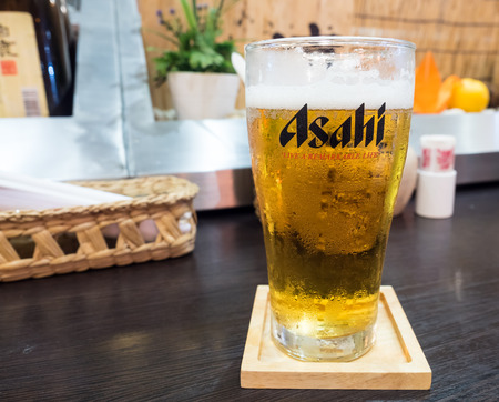 BANGOK - AUGUST 1: Asahi beer, famous Japanese brand, with foam in glass on wooden table in restaurant, was taken on August 1, 2015, in Bangkok, Thailand