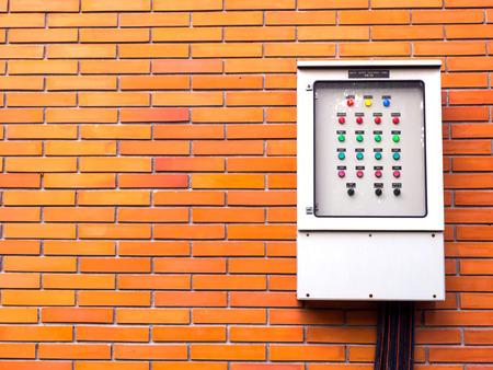 metal box: Orange brick wall with electricity control metal box