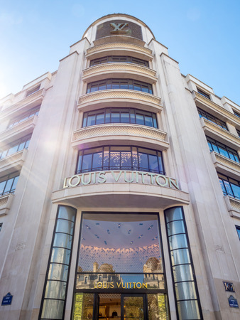 louis vuitton: PARIS - SEPTEMBER 28: Large branch of Louis Vuitton shop on Champ Elysee avenue in Paris, France, with sunlight flare side light, was taken on September 28, 2015.