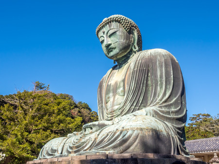 kamakura: The Great Buddha statue of Kamakura (Daibutsu) in the Kotoku-in Temple, Japan, under clear blue sky.