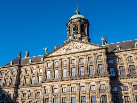 golden age: The front of Royal Palace at the Dam Square, Amsterdam, built as city hall during the Dutch Golden Age in the seventeenth century, under blue sky