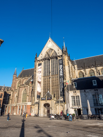 dam square: AMSTERDAM - OCTOBER 2: Tourists in front of the Nieuwe kerk (New church) located on Dam square. The building is used for exhibition space and as museum, under clear blue sky, on October 2, 2015 in Amsterdam, Netherlands.