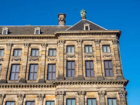 seventeenth: The front of Royal Palace at the Dam Square, Amsterdam, built as city hall during the Dutch Golden Age in the seventeenth century, under blue sky