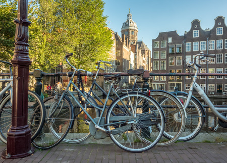 red light district: AMSTERDAM - OCTOBER 2: Saint Nichlas church front of  red light district under blue sky with bicycles and warm morning scene in Amsterdam, Netherlands, was taken on October 2, 2015. Editorial