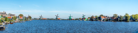 zaan: Panoramiv view of Zaan Schans, popular attractions in Netherlands, has a collection of well-preserved historic windmills and houses, this panoramic view from bridge under blue sky