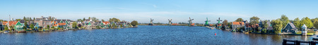 zaan: Zaan Schans is popular attractions in Netherlands, has a collection of well-preserved historic windmills and houses, this panoramic view from bridge under blue sky