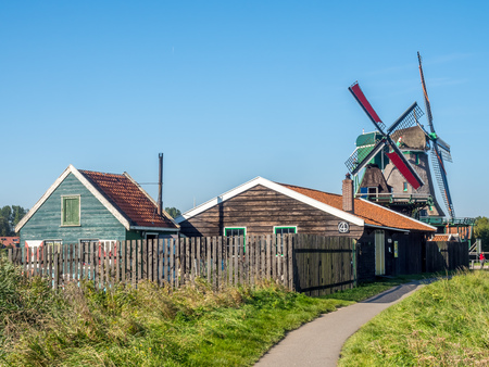 zaan: ZAAN SCHANS - OCTOBER 2: City scene and historic classic windmills with tourists in Zaan Schans under blue sky, Netherlands, on October 2, 2015. Editorial