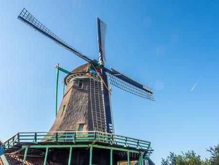 zaan: Historic classic windmill near bank under clear blue sky in Zaan Schans, Netherlands