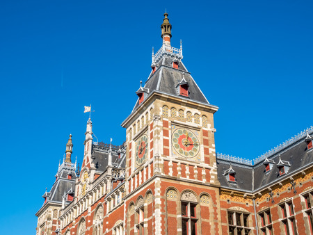 outstanding: Outstanding beautiful architecture of Amsterdam train station building under blue sky, Netherlands