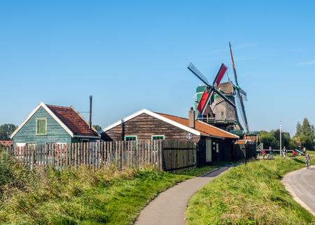 zaan: ZAAN SCHANS - OCTOBER 2: City scene and historic classic windmills with tourists in Zaan Schans under blue sky, Netherlands, on October 2, 2015. Editorial