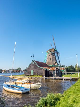 zaan: Historic classic windmill with cruising boats near bank under clear blue sky in Zaan Schans, Netherlands Stock Photo