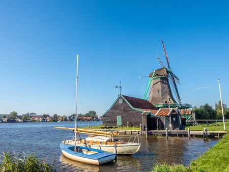 zaan: Historic classic windmill with cruising boats near bank under clear blue sky in Zaan Schans, Netherlands Stock Photo