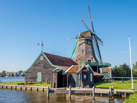 zaan: Historic classic windmill near bank under clear blue sky in Zaan Schans, Netherlands