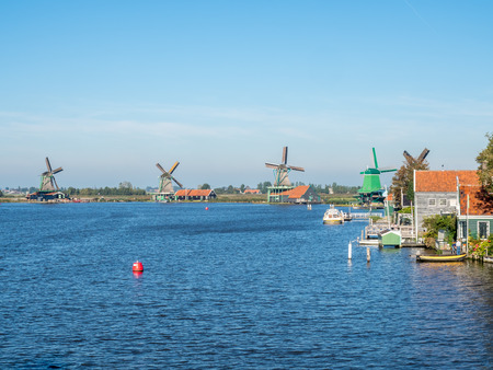 zaan: Zaan Schans is popular attractions in Netherlands, has a collection of well-preserved historic windmills and houses, this view from bridge under blue sky Stock Photo