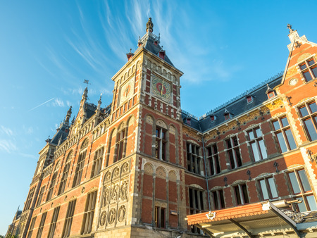 outstanding: Amsterdam train station building is outstanding with unique architecture design under afternoon sunlight under cloudy blue sky