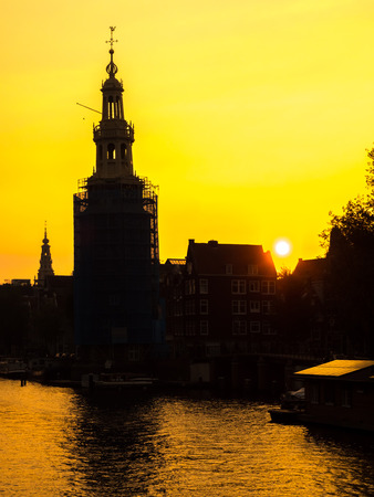 technique: Silhouette technique of clock tower along canal in Amsterdam under golden light sky in evening