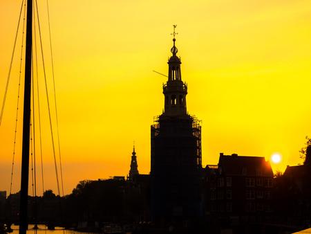 techniek: Silhouet techniek van de klokkentoren langs kanaal in Amsterdam onder gouden licht hemel in avond Redactioneel