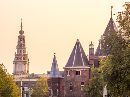 old church: AMSTERDAM - OCTOBER 4: Clock tower of The Old Church in Amsterdam with bicycles on bridge cross canal under evening sky in Netherlands, on October 4, 2015. Editorial