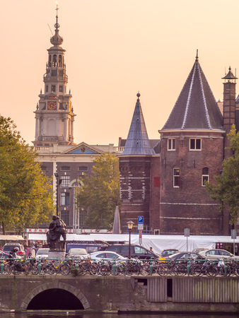 evening church: AMSTERDAM - OCTOBER 4: Clock tower of The Old Church in Amsterdam with bicycles on bridge cross canal under evening sky in Netherlands, on October 4, 2015. Editorial
