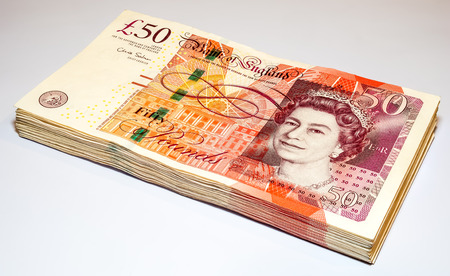 BANGKOK - FEBRUARY 28: Stack of fifty pounds British bank notes placed on white background with light and shadow technique, was taken on February 28, 2016, in Bangkok, Thailand.