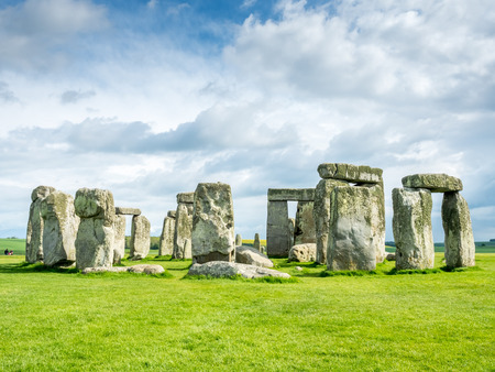 unrecognized: Stonehenge an ancient prehistoric stone monument near Salisbury, Wiltshire, England, with unrecognized tourist nearby.