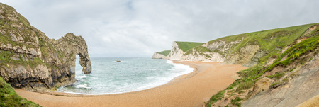 durdle door: Panoramic view of Durdle door is natural limestone arch at coastline, with surrounding cliff and coastline under rain cloudy sky,  located at Dorset in England