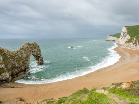 'rock drill': Durdle door is natural limestone arch at coastline, with surrounding cliff and coastline under rain cloudy sky,  located at Dorset in England