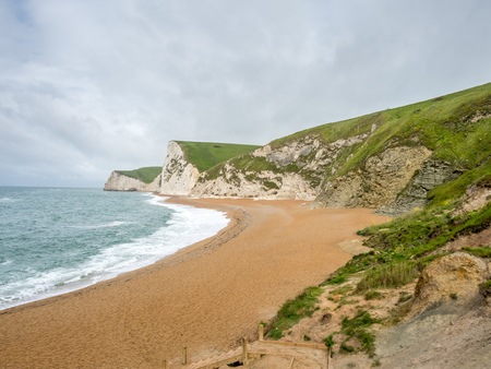 durdle door: Durdle door is natural limestone arch at coastline, with surrounding cliff and coastline under rain cloudy sky,  located at Dorset in England