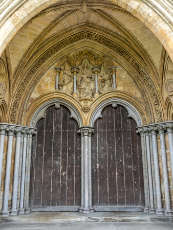 british weather: Door arch of Salisbury cathedral, outstanding with English gothic architecture, in Salisbury, England. Stock Photo