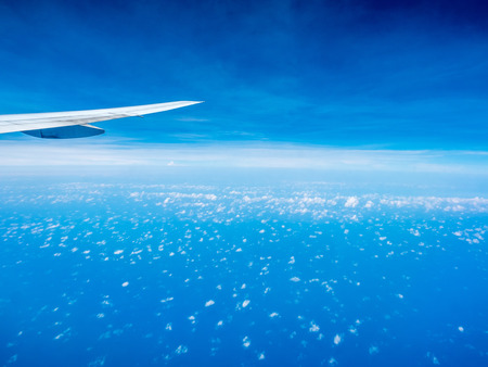 puffy: Small puffy cloud on blue sky with aircraft wing from aircraft window view