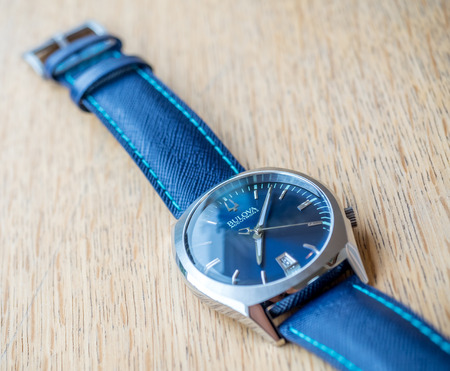 hertz: BOURNMOUTH - MAY 18: Blue dial and blue leather strap Bulova watch on wooden table with natural morning light