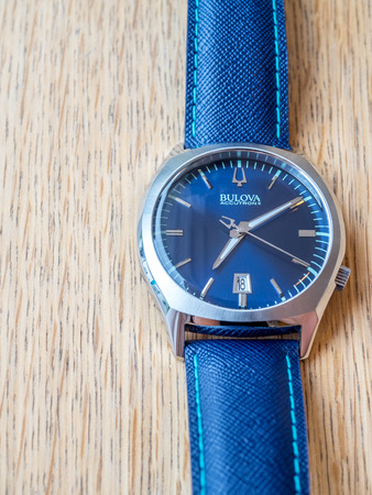 tuning fork: BOURNMOUTH - MAY 18: Blue dial and blue leather strap Bulova watch on wooden table with natural morning light
