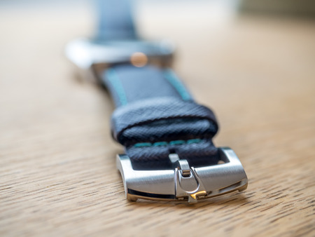 tuning fork: Blue dial and blue leather strap watch on wooden table with natural morning light Editorial