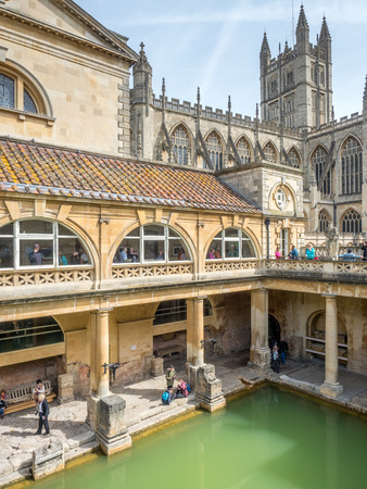 world heritage site: BATH - MAY 19 : Roman Bath, the UNESCO World Heritage site, with The Bath Abbey behind under cloudy sky and green colour water in Roman Bath