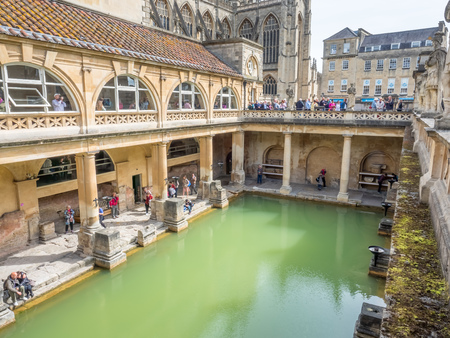 unesco world heritage site: BATH - MAY 19 : Roman Bath, the UNESCO World Heritage site, with The Bath Abbey behind under cloudy sky and green colour water in Roman Bath