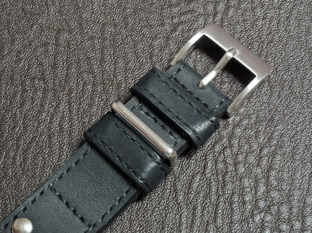 cuero vaca: Genuine cow leather watch strap with stainless steel buckle on black stamped leather floor
