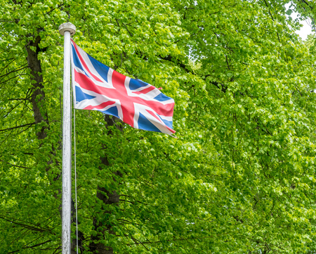 flagstaff: Union Jack flag on flagstaff in outdoor park with green leaves background Stock Photo