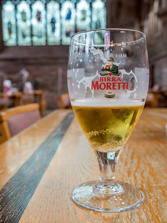 CHESTER - MAY 20 : A glass of Birra Moretti beer was bought inside of Chester Cathedral place on woode table, Chester city, England, was taken on May 20, 2016.