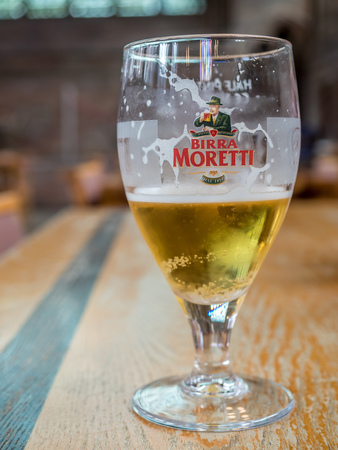 chester: CHESTER - MAY 20 : A glass of Birra Moretti beer was bought inside of Chester Cathedral place on woode table, Chester city, England, was taken on May 20, 2016.