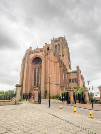 largest: Exterior architecture of Liverpool cathedral, the fifth largest cathedral in the world, under cloudy sky in England