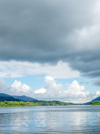 Lake side coast view with mountain background under cloudy evening twilight sky Stock Photo