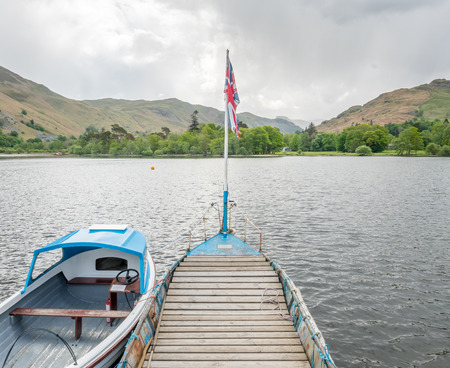 lake sunset: Yacht in rural pier in lake with mountain background under cloudy sky in countryside of England Stock Photo