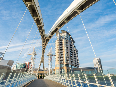 Salford quays lift bridge, known as Millenium footbridge, crossing Manchester ship canal in Mancherster city, England, under cloudy sky in evening time