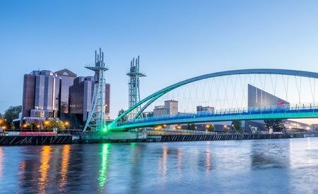 Salford quays lift bridge, known, as Millenium footbridge, is landmark of Manchester, England, under twilight evening sky Editorial