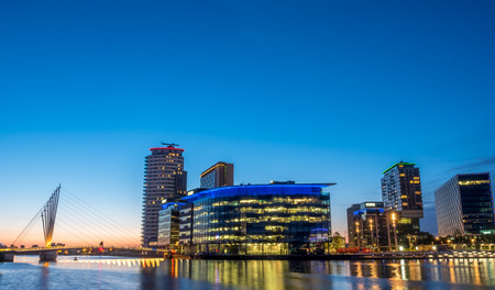 MANCHESTER - MAY 22: Foot bridge cross Manchester ship canal, connecting between BBC Media City, ITV studio buildings and Imperial War Museum at Salford quays in Manchester city, England, under twilight sky, on May 22, 2016. Editorial