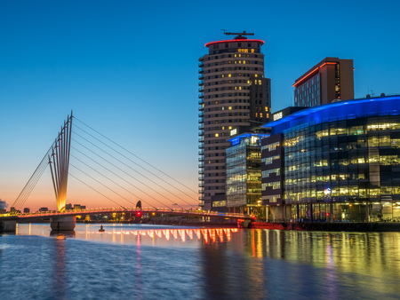 bbc: MANCHESTER - MAY 22: Foot bridge cross Manchester ship canal, connecting between BBC Media City, ITV studio buildings and Imperial War Museum at Salford quays in Manchester city, England, under twilight sky, on May 22, 2016. Editorial
