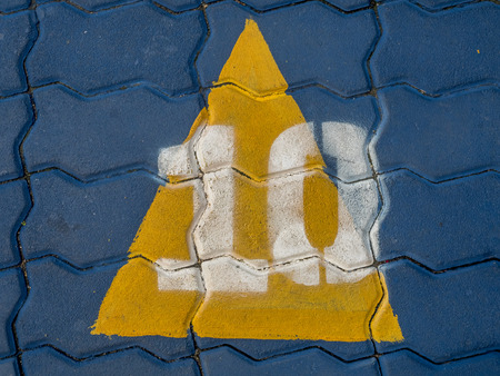 numero diez: Number ten cover with yellow triangle on blue brick floor