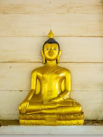 thai buddha: Golden buddha statue sit in meditation posture on wall of Thai temple main church building