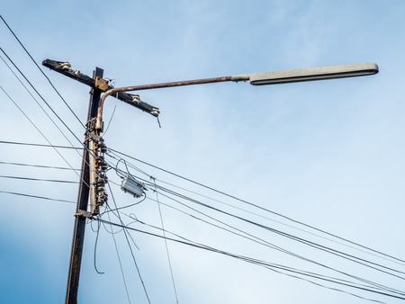 untidy: Untidy, not organized, electricity and lamp post with telecommunication wires under blue sky Stock Photo