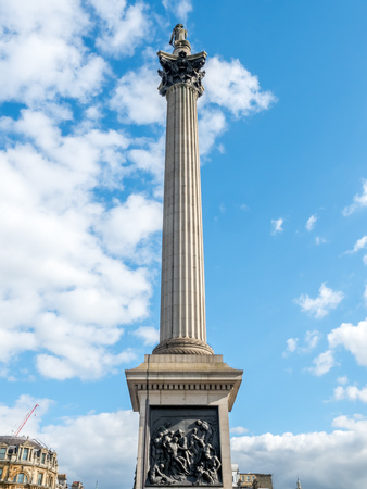 trafalgar: The Nelson column in Trafalgar square under cloudy blue sky in London, England